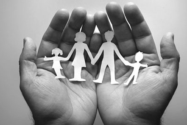 Black and white photo of a pair of hands holding white cutouts of four people being a family