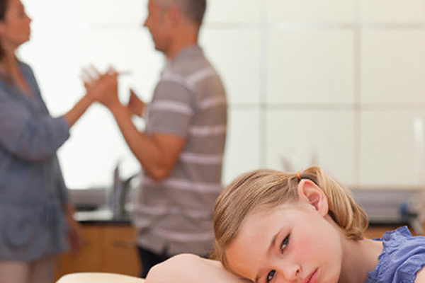 Mom and dad arguing in background while a little girl rests her head on a table with a sad face