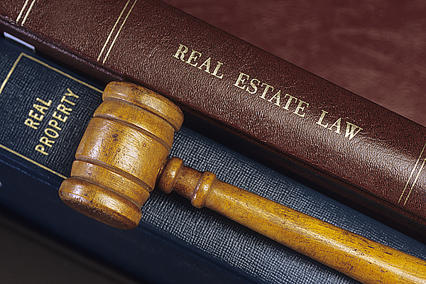 a wooden gavel placed upon two leather bound books titled real estate law and real property