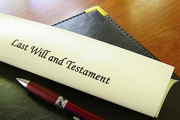 last will and testament document on a leather portfolio and a pen