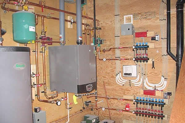 tanks, pipes, and a hot water tank mounted on a wall