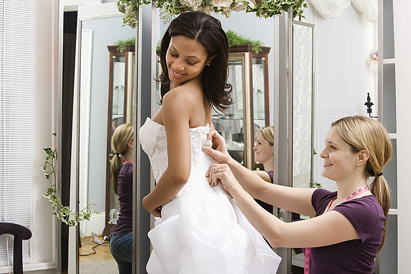 a lady pinning the back of a dress for alterations