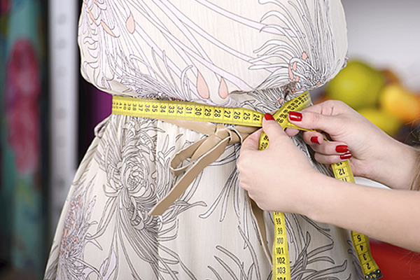 a yellow measuring tape under the bosom of a mannequin wearing a dress