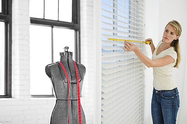 a woman measuring horizontal blinds with a measuring tape and a mannequin with a pink measuring tape over its shoulder area