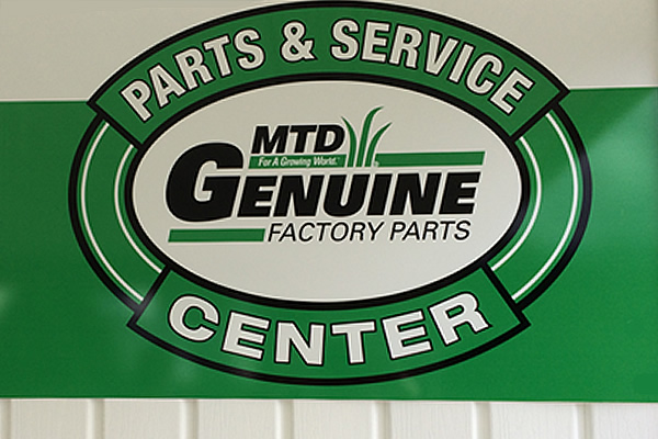 exterior green and white sign advertising M T D genuine factory parts