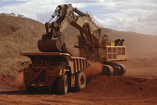 haul truck backed up to a back hoe dumping a load of dirt into the box