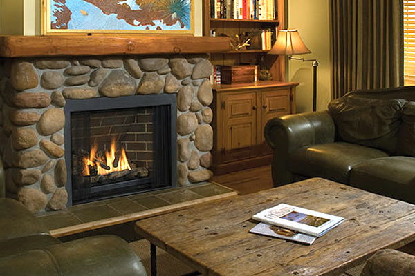 cozy fire roaring in a gas fireplace in a living room with rock work displayed for accent