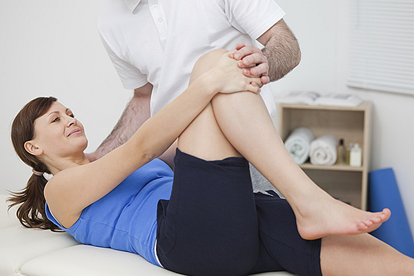 Physiotherapist working on knee exercises with a client