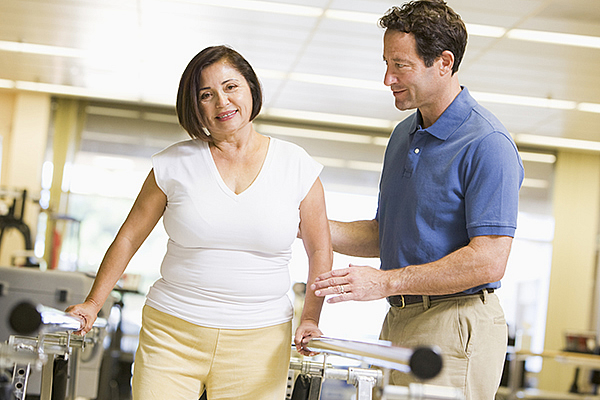 Physiotherapist helping a client walk