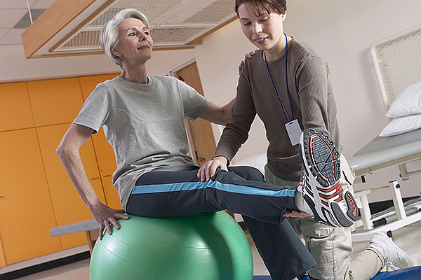 Physiotherapist working on exercises with an elderly client