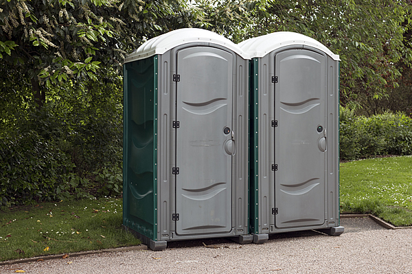 two stand up portable toilets that are used for rental purposes at outdoor events