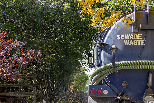 blue sewage waste truck with a holding tank parked outside