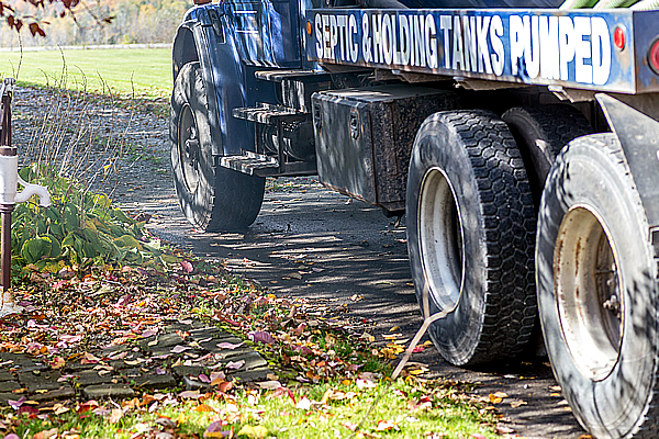 a side view of a blue septic truck
