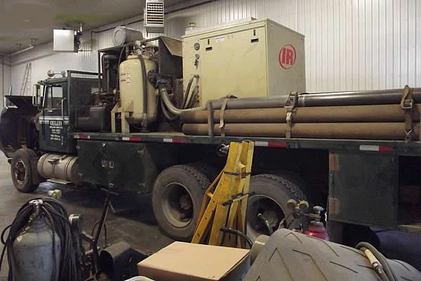 haul truck in the shop with a trailer loaded up with metal piping