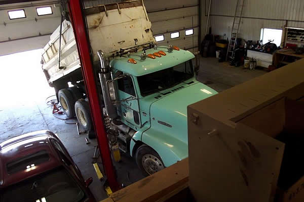 turquoise coloured dump truck parked in the shop