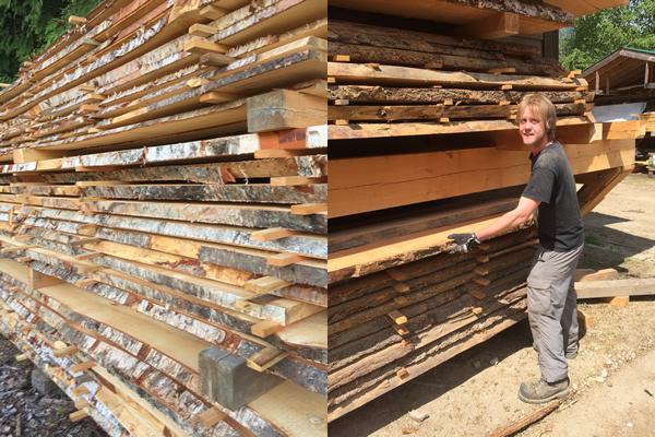 man standing outside next to high piles of horizontally cut wood