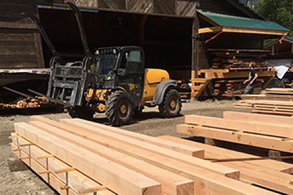 forklift onsite at a mill moving piles of lumber to different ends of the yard