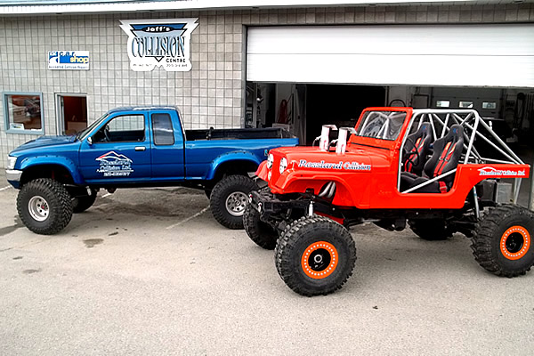 blue truck advertising Rossland Collision parked next to an orange lifted jeep