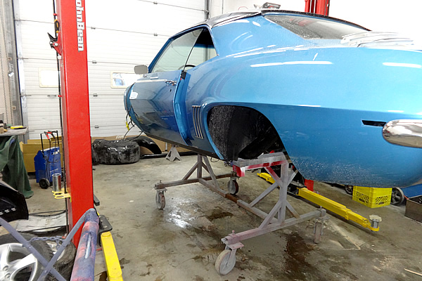 body of a light blue car on a hoist with no engine or tires