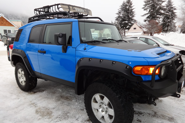 blue F J parked outside in the snow