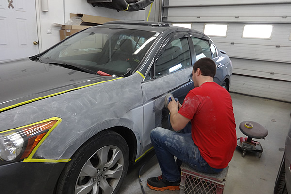 man sitting down detailing the exterior of a gray coloured car door on the driver's side