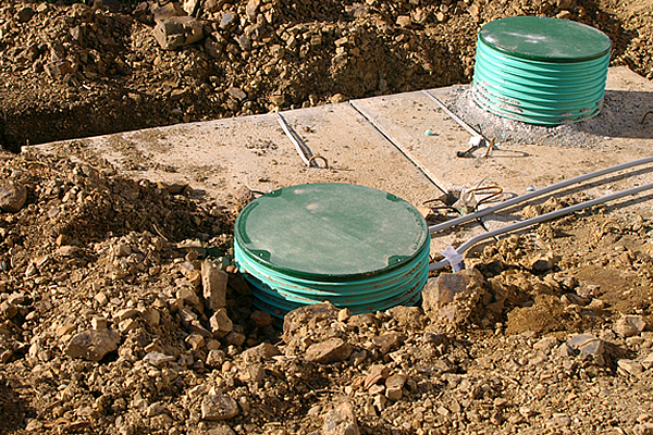 installed septic tank showing a wooden cover and two green circular tubes with covers