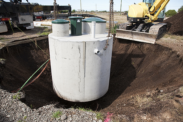 green and white septic tank being installed into the ground