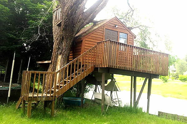 wooden play house built in a tree with wrap around stairs