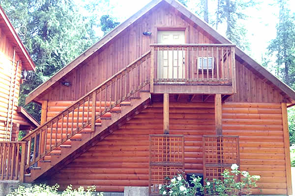 wooden and log cabin with stairs leading up to a top-floor door