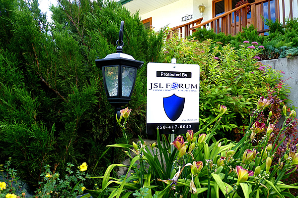 black outdoor lamp next to a white sign advertising the premises are protected by J S L Forum