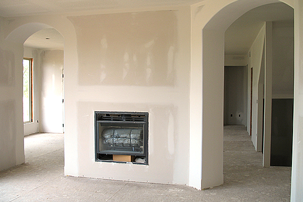 new drywall construction in a residential sitting room with archways