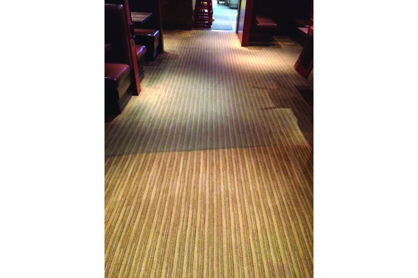 Half cleaned carpet at a high traffic area in restaurant