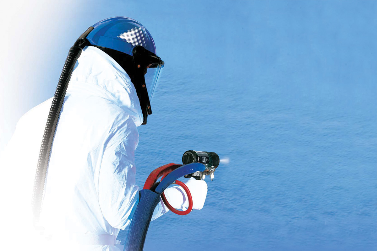 man spraying insulation on a blue coloured wall