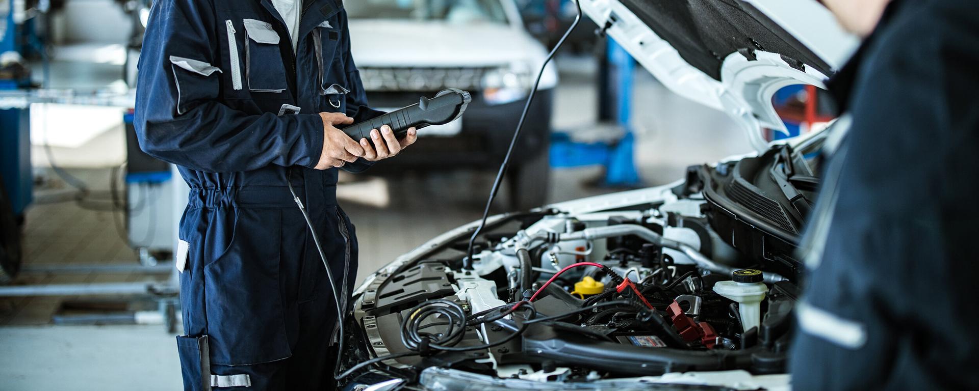 Two mechanics use a computer to diagnose car mechanical problems.