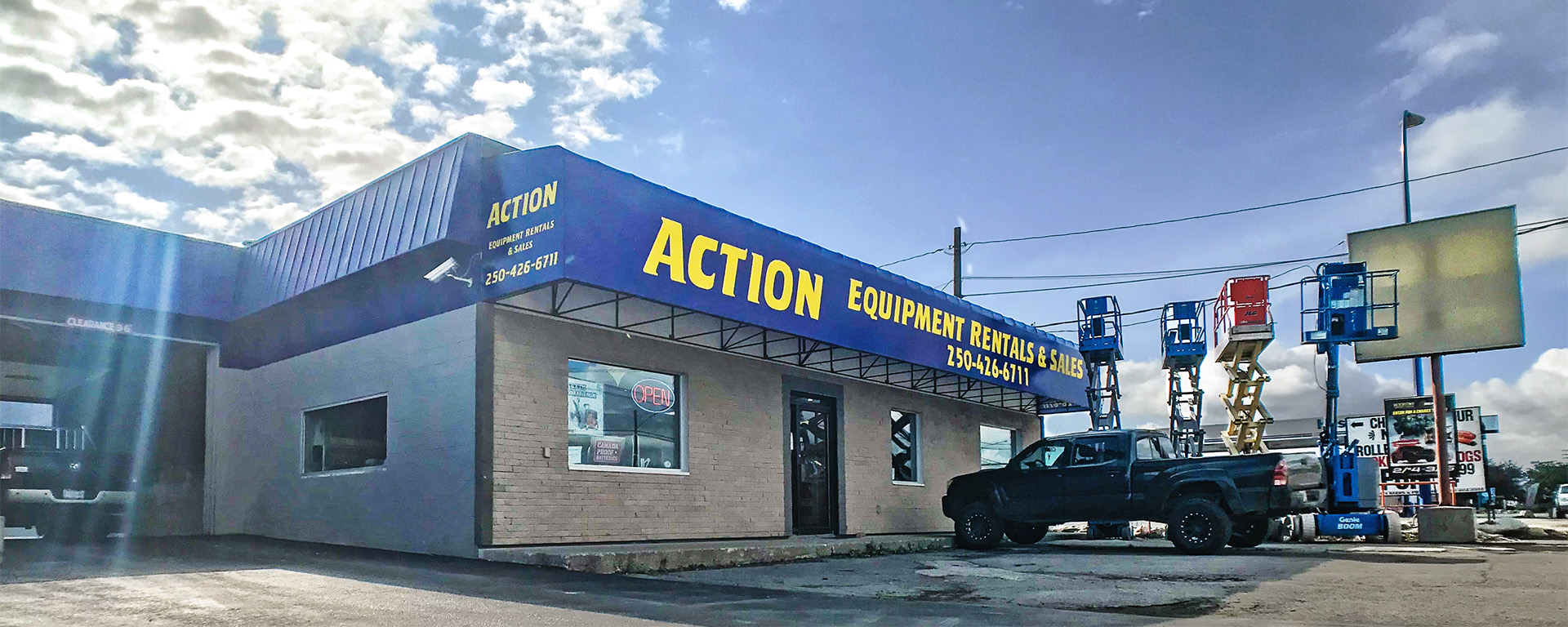 Front entrance of Action Equipment Rental is a grey building with a blue awning and yellow lettering.