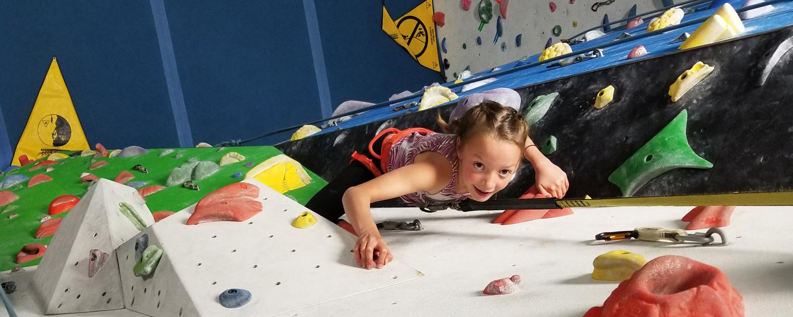 A young girl smiling while climbing up a wall at Arq Mountain Centre in Cranbrook