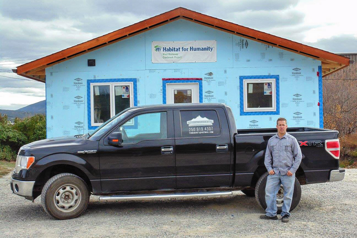 Kevin Johnston, owner of Kootenay Mountain Metal, standing in front of his truck outside of Habitat for Humanity