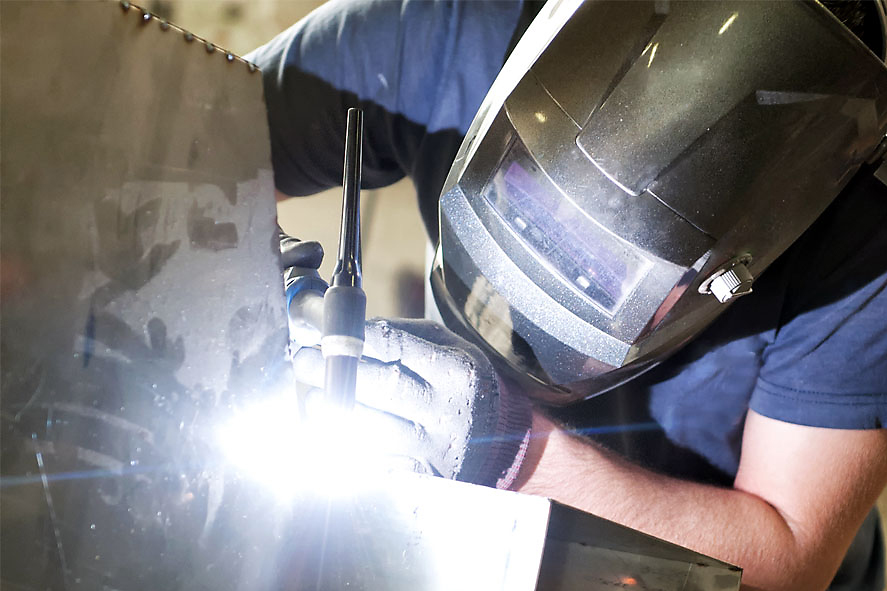 a male welder wearing proper protective equipment welding pipes