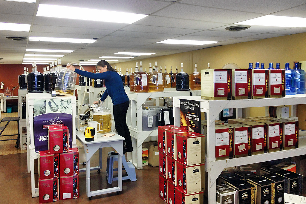 A woman stocking wine of shelves
