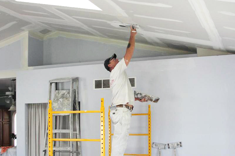 man standing on yellow scaffold plastering drywall on a ceiling